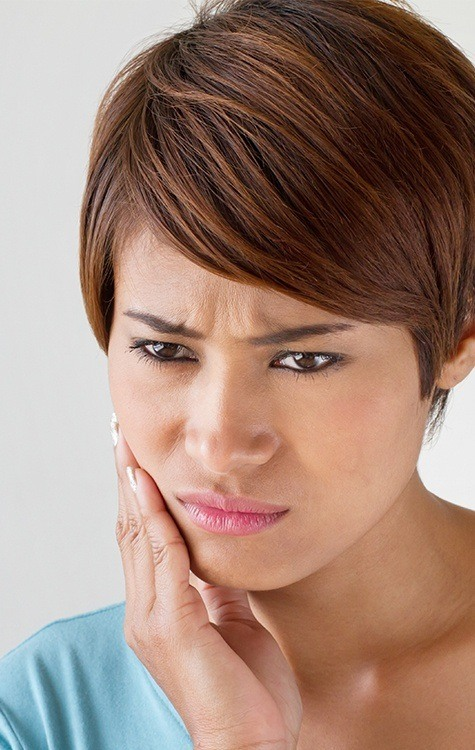 Woman in need of laser dentistry holding cheek in pain