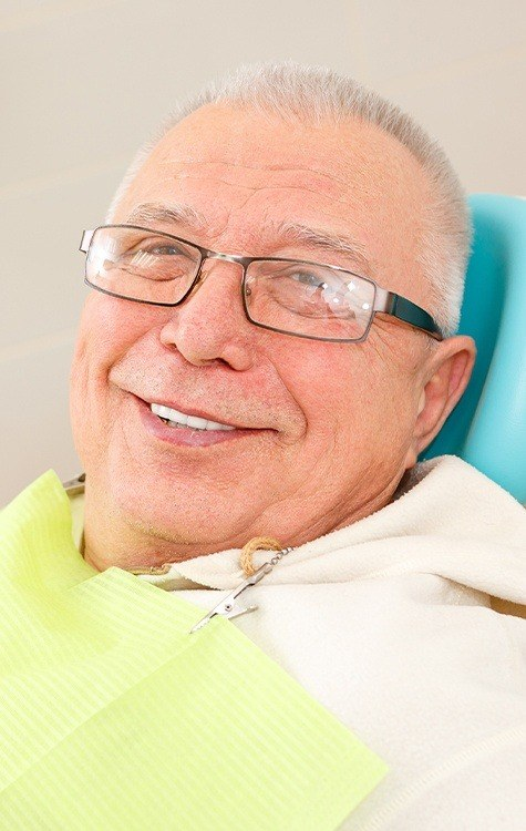 Older man with healthy smile after dental bridge placement