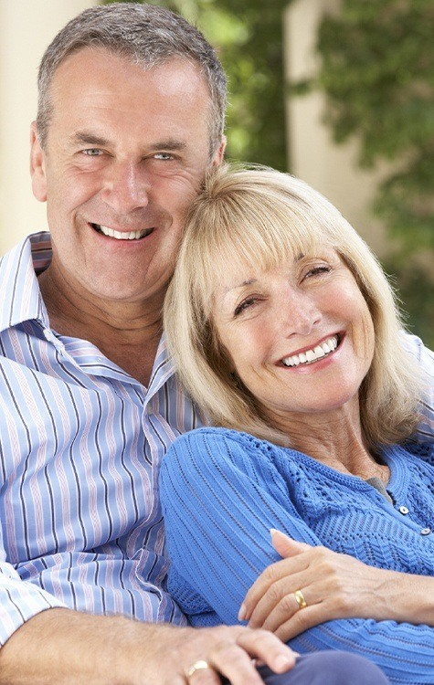 Man and woman smiling after dental bridge placement
