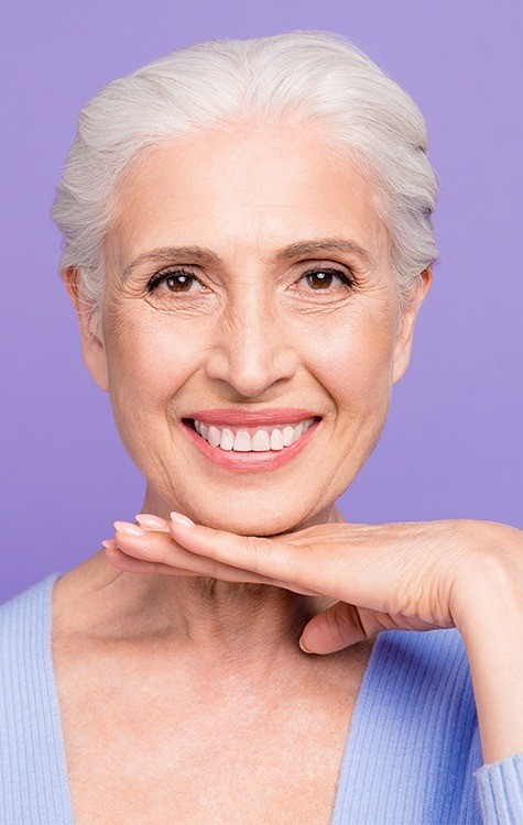 Woman keeping smile healthy with dental implant aftercare
