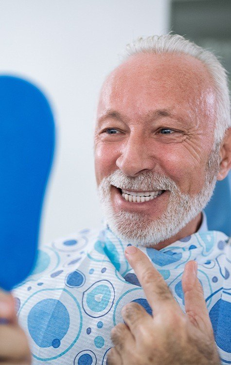 Man pointing to smile during dental implant aftercare visit