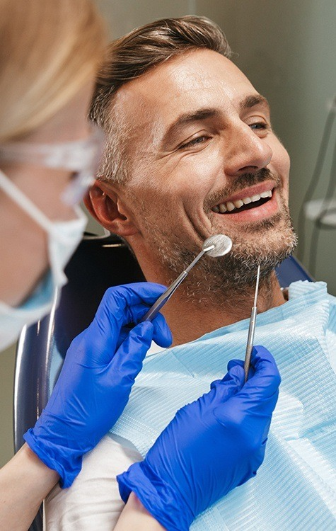 Man receiving a dental implant aftercare exam