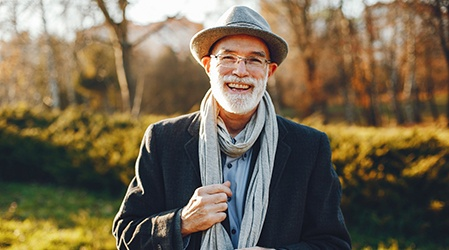 Man smiling outside with dental implants in Frisco