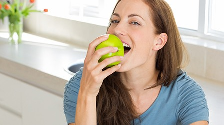 Woman in blue shirt taking a bite of a green apple