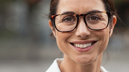 Closeup of woman's face with nice smile and glasses