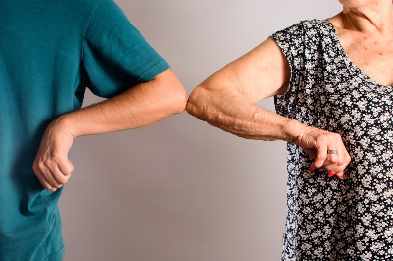 """two individuals performing the """"elbow bump"""" as a way to say hello"""
