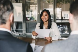 Woman sitting in a job interview smiling and holding a piece of paper